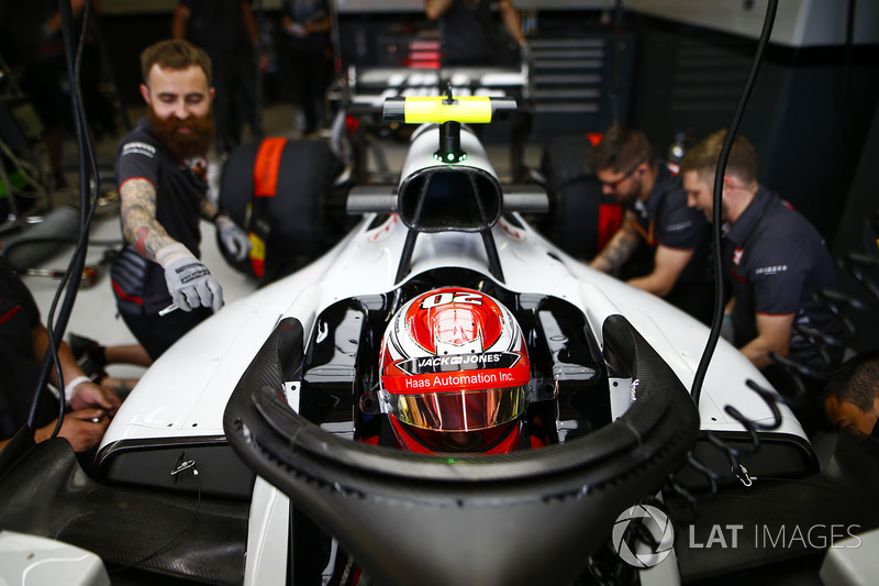 Kevin Magnussen, Haas F1 Team, in cockpit, is attended to by mechanics in the team's garage
