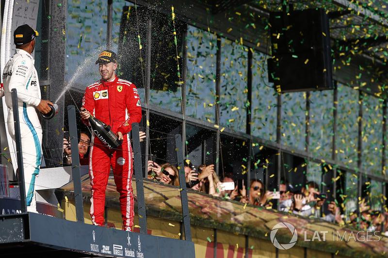 Lewis Hamilton, Mercedes AMG F1, 2nd position, and Sebastian Vettel, Ferrari, 1st position, celebrate with Champagne on the podium