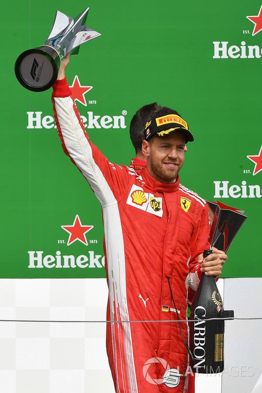 Race winner Sebastian Vettel, Ferrari celebrates on the podium with the trophy