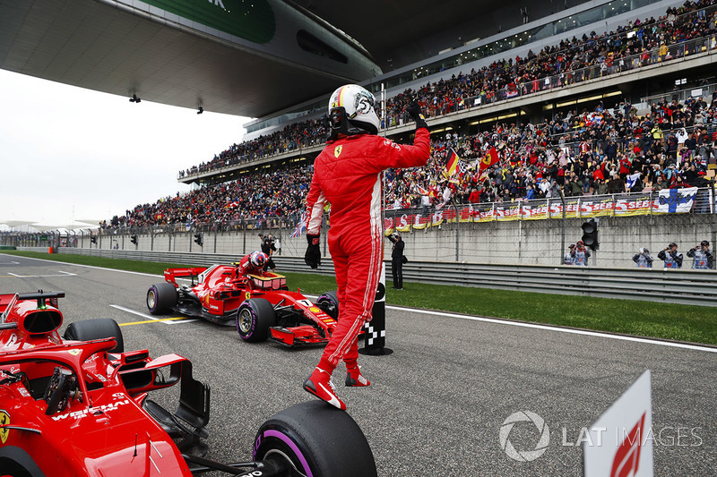 Sebastian Vettel, Ferrari, steps off his front tyre after taking pole position as Kimi Raikkonen, Fe