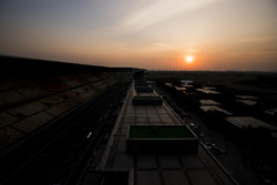 The sun sets behind the paddock