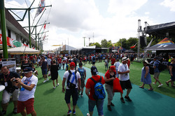 A large contingent of fans walk through an alley of merchandise stands