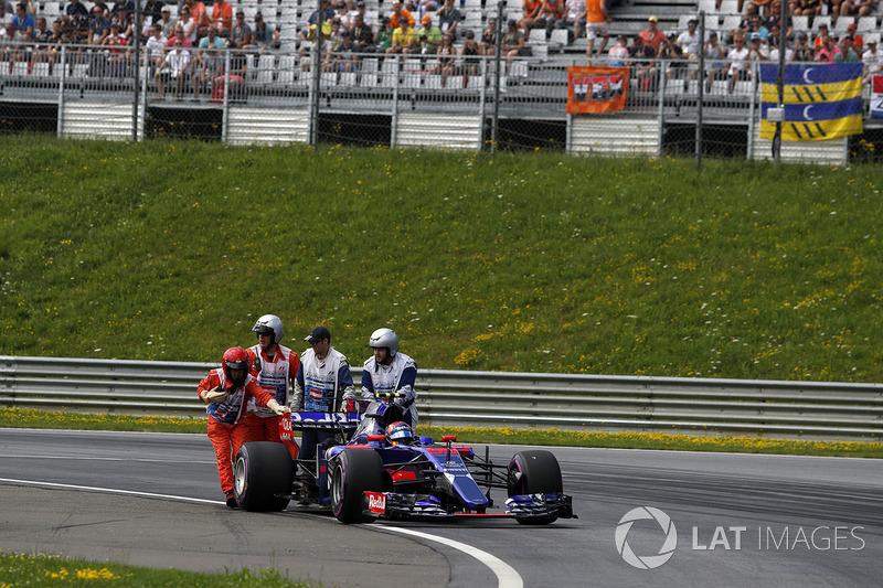 Маршали штовхають зупинившийся болід Карлоса Сайнса-молодшого, Scuderia Toro Rosso STR12, під час третьої практики
