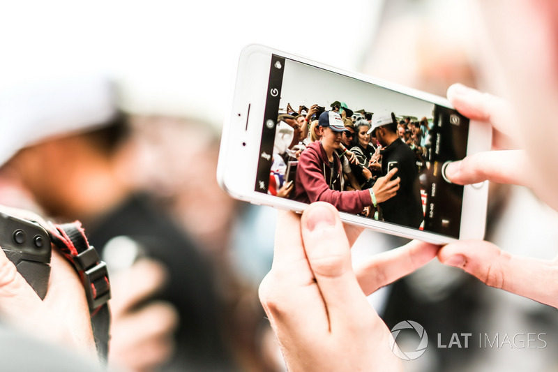 On a phone shows Lewis Hamilton, Mercedes AMG F1 sign autographs for the fans