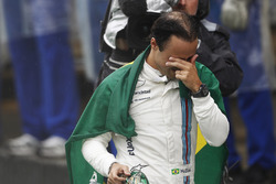 Felipe Massa, Williams, carries a Brazilian flag as he walks back to his garage in tears after crash