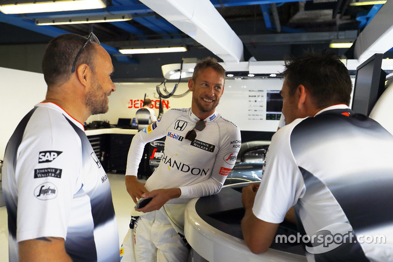 Jenson Button, McLaren talks to colleagues in the garage