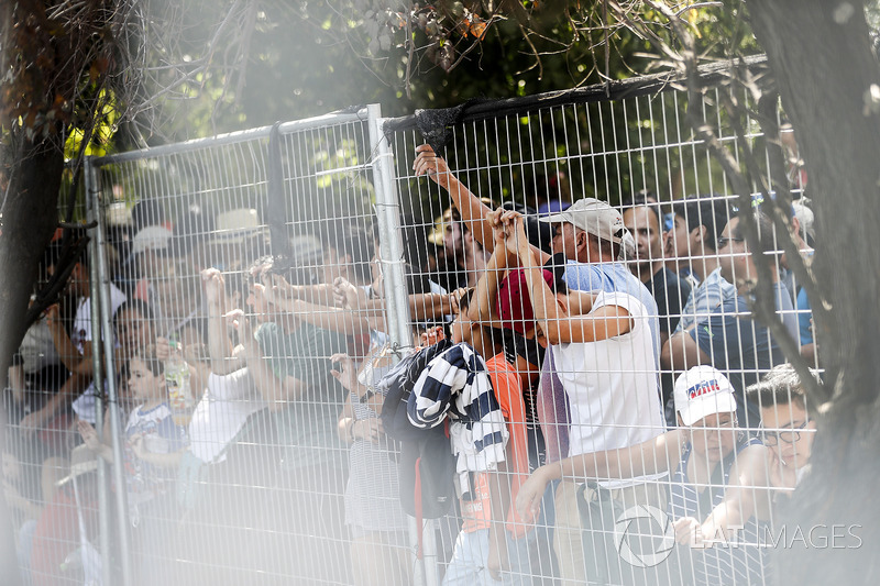 Fans wave to the drivers