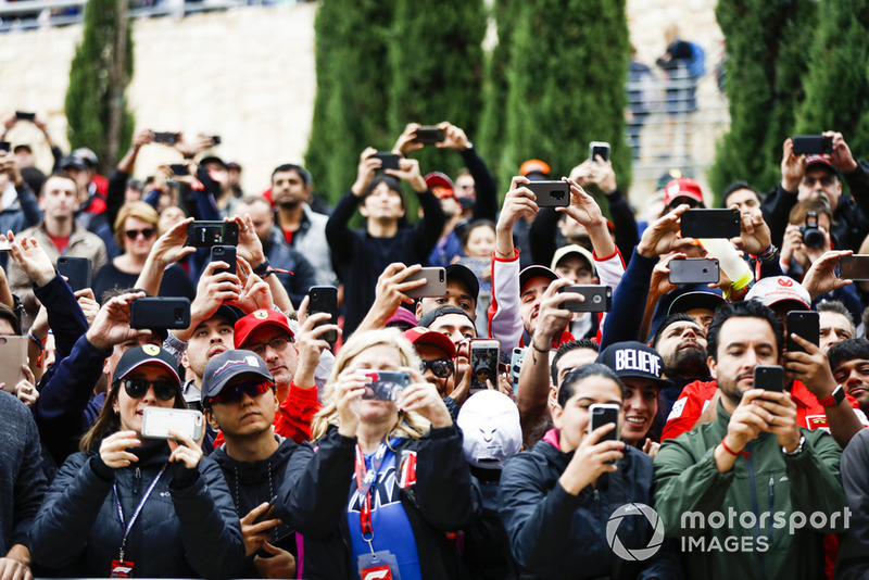 Fans take photos of the drivers with their mobile phones