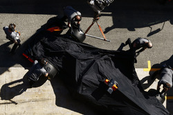 McLaren mechanics push the covered Stoffel Vandoorne McLaren MCL32 into its garage after it encountered a technical problem on track