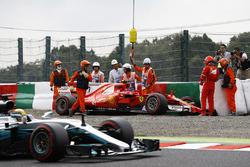 Lewis Hamilton, Mercedes AMG F1 W08, passes the crashed car of Kimi Raikkonen, Ferrari SF70H, as marshals recover it