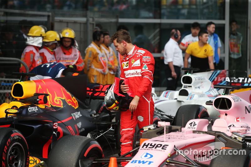 Sebastian Vettel, Ferrari, examines a Red Bull Racing RB13 in parc ferme