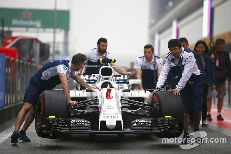Williams team members push a Williams FW40