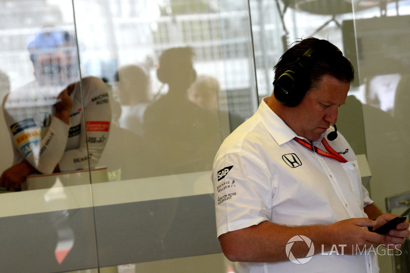 Fernando Alonso, McLaren observa a Zak Brown, Director Ejecutivo de McLaren, que utiliza su teléfono