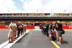 Sean Bratches, Managing Director of Commercial Operations, Formula One Group, Thierry Antinori, Executive Vice President and Chief Commercial Officer, Emirates Airlines, and Chase Carey, Chairman, Formula One, stand opposite photographers with flight atten