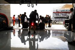 McLaren engineers return Fernando Alonso, McLaren MCL32, to the garage