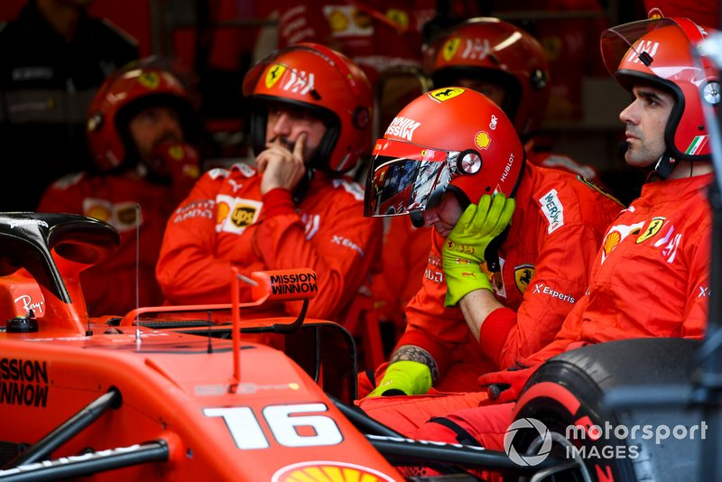 Mechanic sat in the garage next to the retired car of Charles Leclerc, Ferrari SF90