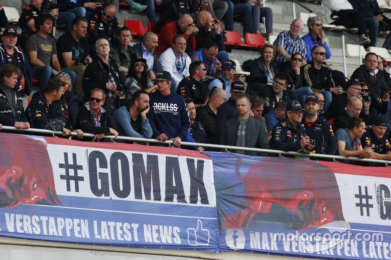 Велика група уболівальників Макса Ферстаппена, Red Bull Racing, сидять над банером на трибуні