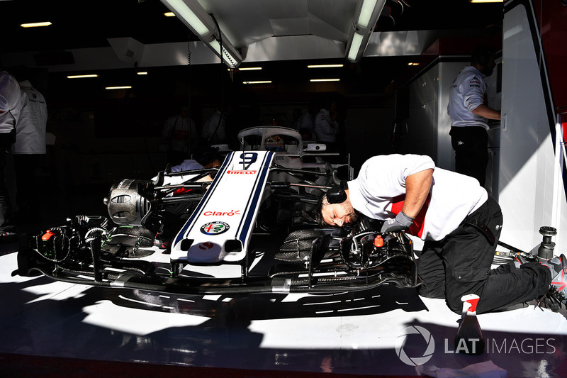 Mechanics work on Alfa Romeo Sauber C37 in the garage