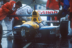 Marshalls get Nigel Mansell's Williams FW14 Renault chassis off the track after his crash into the wall, when he aquaplaned on lap 16