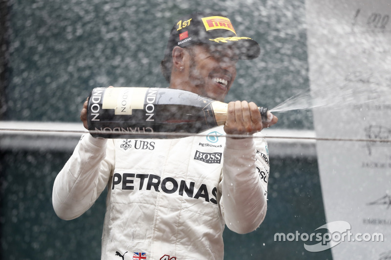 Lewis Hamilton, Mercedes AMG, sprays the victory Champagne on the podium