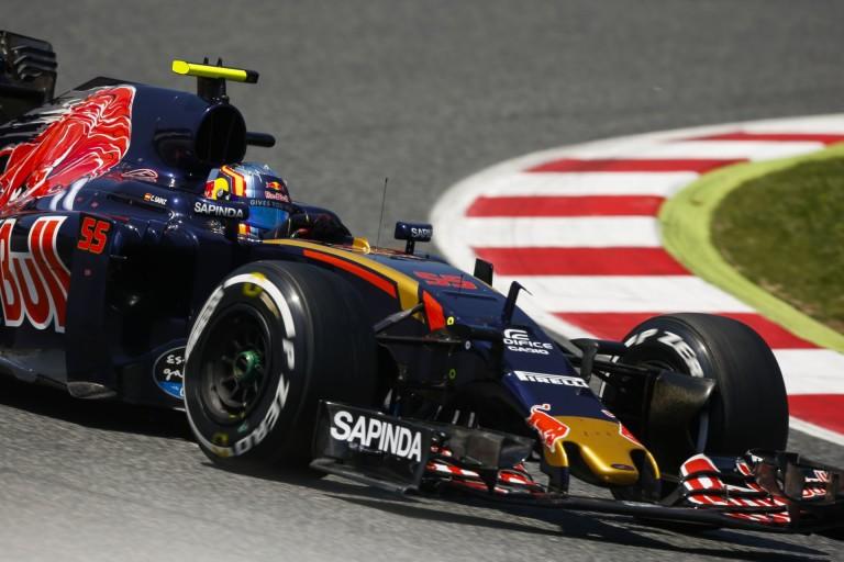 Sainz és a jelenet, amikor a zászlóval a kezében ünnepel az F1-es gép volánja mögött