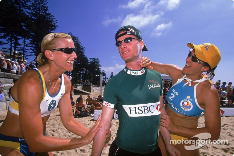 Eddie Irvine having suncream put on him by Australian Olympic Beach Volleyball gold medalists Kerry