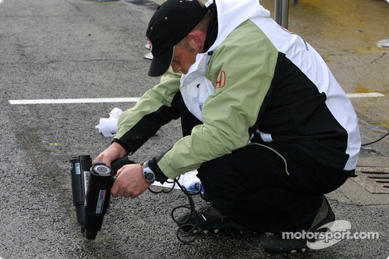 Un miembro del equipo BAR secando la zona de pits