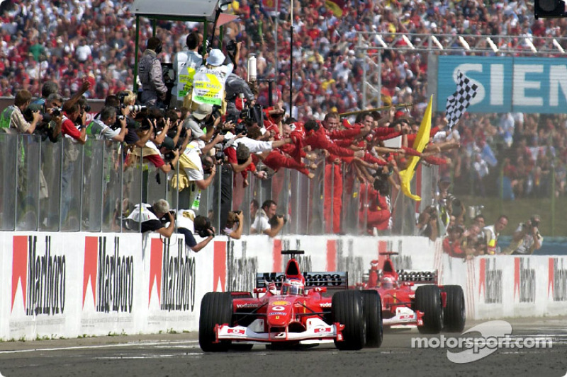 Rubens Barrichello tomando la bandera a cuadros delante de Michael Schumacher