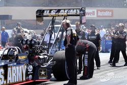 The crew wipes down Tony Schumacher's tires