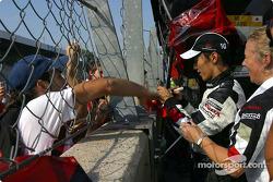 Takuma Sato signs autographs after the race