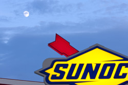 The moon rises over the Sunoco sign in the infield
