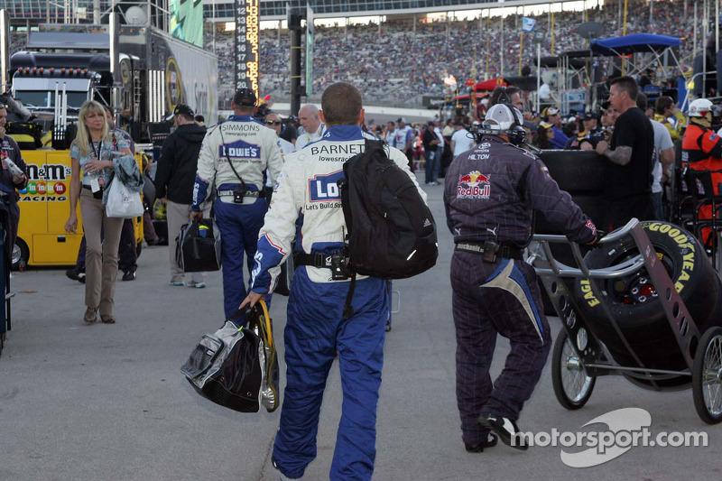 Teamleden van Jimmie Johnson lopen in de pitstraat nadat ze zijn vervangen door de crew van Jeff Gordon's