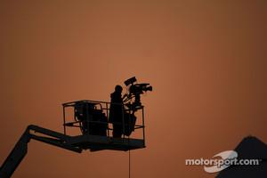 A television camera man at sun set.