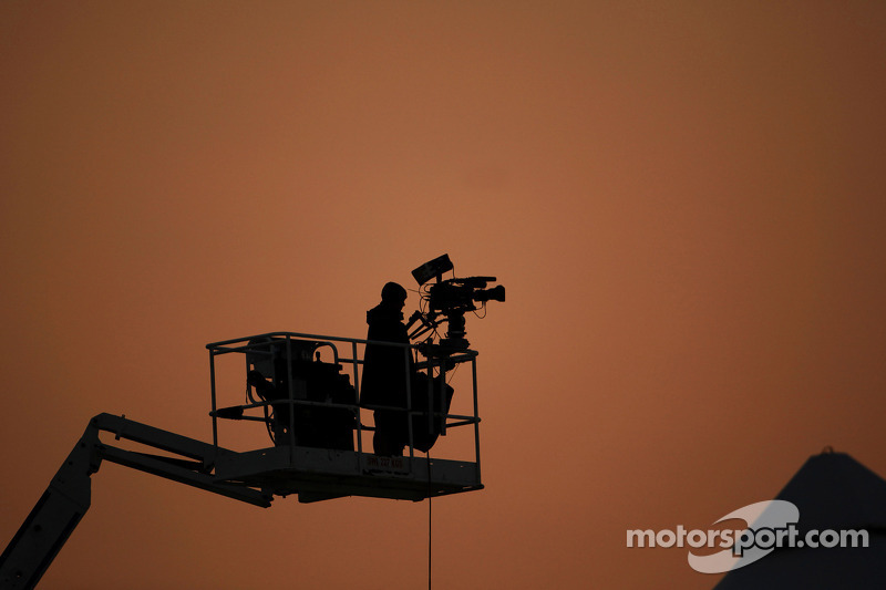 A television camera man at sun set.
