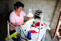 Leyder Zapata, of Avon's Alterations, sews sponsor patches onto teams' firesuits