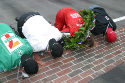 Kim Green, Kevin Savoree, Dan Wheldon and Michael Andretti kiss the bricks in celebration of the victory