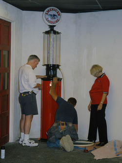 Susan Unser supervises installation of visible gasoline pump given to Al Unser, Jr. as a gift from Valvoline