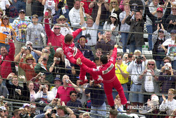 Gil de Ferran and Helio Castroneves clasp hands in victory while hanging on the fence