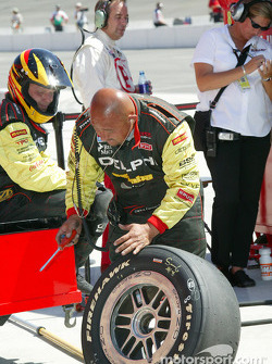 Kelley Racing team member checks tires