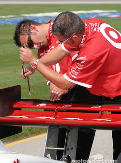 Chip Ganassi Racing crew members adjust rear wing