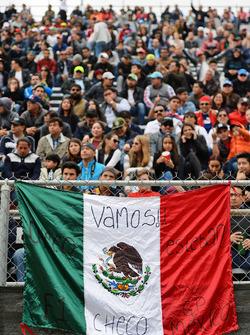 Fans en la tribuna y una bandera mexicana