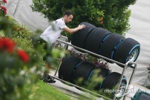 A Mercedes GP mechanic wheels wet Pirelli tyres through the paddock