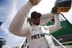 Lewis Hamilton, Mercedes AMG F1, shows off his Ayrton Senna helmet, a gift after equalling the Brazilian's pole record, to fans.