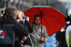 Lewis Hamilton, McLaren walks through the pits with an umbrella
