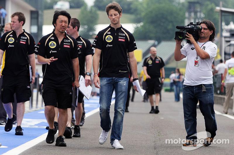 Romain Grosjean, Lotus F1 Team wandelt op het circuit met Ayao Komatsu, Lotus F1 Team Race Engineer