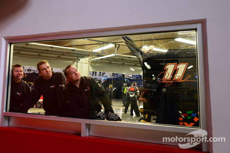 Team members watch practice action on a big screen