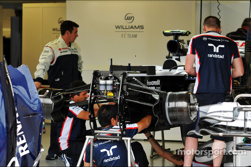 A Williams FW35 is prepared by mechanics in the pits