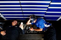 Hendrick Motorsports crew members wait for the rain to stop