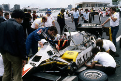 Alain Prost and his mechanics work on the Renault RE30B on the grid