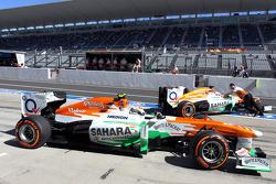 Adrian Sutil, Sahara Force India VJM06 en teamgenoot Paul di Resta, Sahara Force India VJM06 in de pits